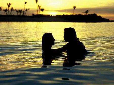 Romantic Couple in water at Sunset Stock Photo