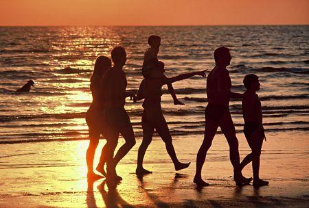 Family walking along beach at Sunset Stock Photo
