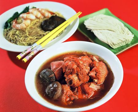 Asian dish of Chicken and Mushroom, with Prawns and Noodle dish in background Stock Photo
