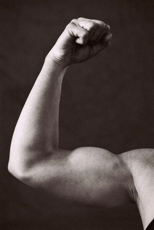 Female Bodybuilder in competition pose, photographed on Infra Red Black and White film, detail of flexed Bicep, intentional grain