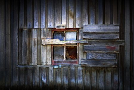 Close up detail of window in side of old timber barn building on farm