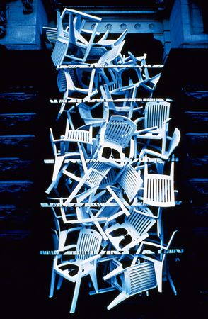 infra red: Plastic Chairs stacked in archway , photographed on color infra red film(grainy)