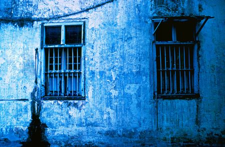 Detail of windows and blue wall on the side of a derlict building. Photographed on Infra Red film(grainy)