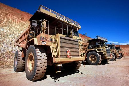 Row of Dump Trucks at Open Cut Gold Mine Stock Photo