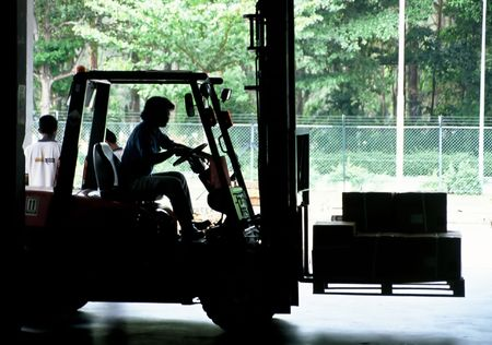 Fork Lift moving freight inside warehouse Stock Photo