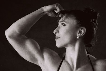 female form: Female Bodybuilder in competition pose, photographed on Infra Red Black and White film, intentional grain