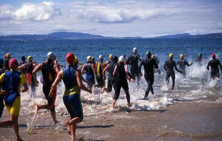 Competitors in Triathlon entering the water for the swimming leg Stock Photo