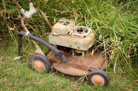 uncut: Tosaerba Rusty Old sembra essere stato lasciato in mezzo all'erba alta uncut Archivio Fotografico
