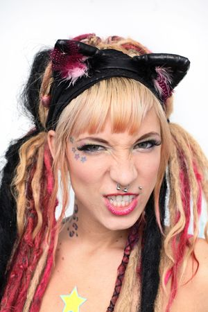 snarl: Portrait of young aggressive woman with piercings, tattoos and dreadlocks