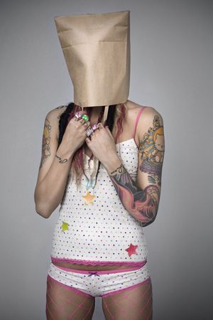 shame: Young woman with Tattoos and her hair in colorful dreadlocks with a paper bag over her head