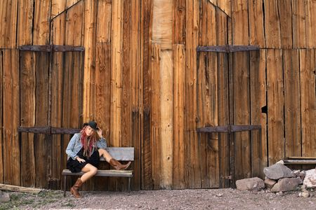Young woman in Cowgirl style clothing sitting outside an old timber barn Stock Photo - 4788183