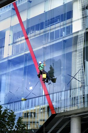 cleaning an office: Professional window washer cleaning large windows of a new office building
