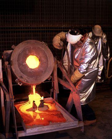 mijnbouw: Goudmijn werknemer giet gesmolten goud in ingots schimmel Stockfoto