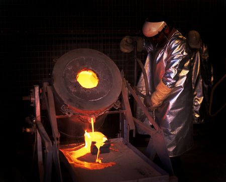 Gold mine worker pours molten Gold into ingot mold photo