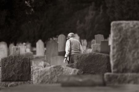 headstones: View of various sandstone and marble headstones with an old man walking in an old graveyard