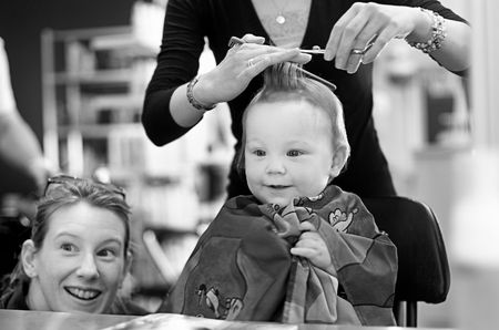 Eighteen month old boy having his first haircut at the Hairdressers photo