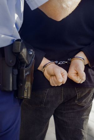 arrested criminal: A criminal in handcuffs is being escorted by a Police Officer