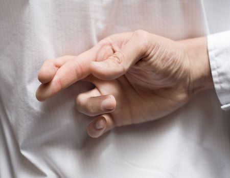 mislead: Close up detail of fingers crossed behind a male back Stock Photo