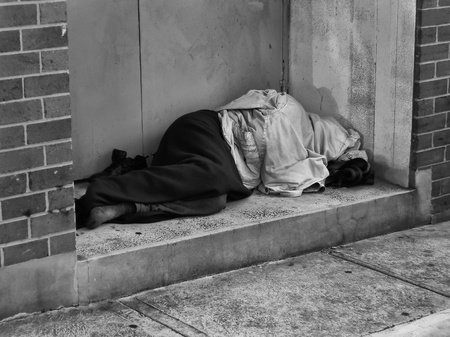homeless people: A Homeless Man bundled up under a jacket asleep in a city doorway