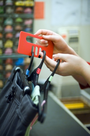 shoplifter: A female shop assistant at change room tags clothes for security