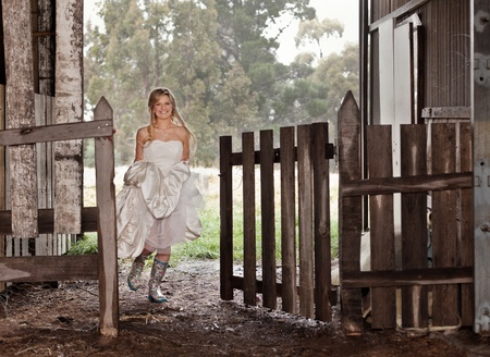 gumboots: Beautiful young bride running through gate wearing bright colorful rubber boots Stock Photo