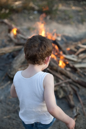 seven year old: Seven year old boy in white singlet watching a Bonfire