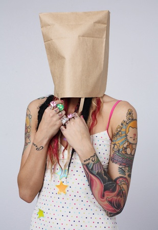 Young woman with Tattoos and her hair in colorful dreadlocks with a paper bag over her head