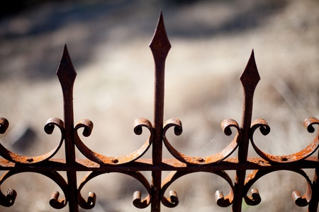 View of wrought iron decorative fence surrounding a gravesite in an old graveyard Stock Photo