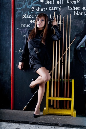 pool room: Beautiful woman  in short black dress playing in a pool room with eight ball cues