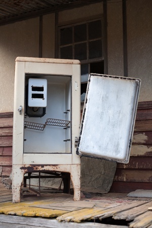 icebox: A old vintage refrigerator left outside an abandoned home