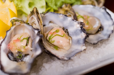 A restaurant of Oysters in the shell, served with lemon on a bed of Rock Salt