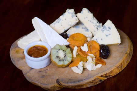 penicillium: A cheese platter featuring blue vein and camembert cheeses, dried fruits, kiwi fruit