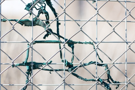 Abstract view of wire mesh fence with remnants of green shade cloth Stock Photo - 10692553