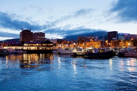 tasmania: Hobart waterfront photographed at night with city skyline and fishing boats