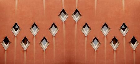 ochre: Abstract Patterns of diamond shaped windows on an ochre coloured wall