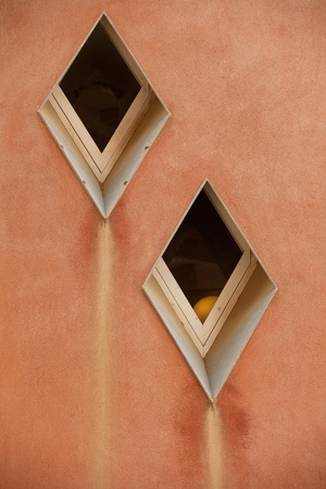 ochre: Diamond shaped abstract windows on an ochre coloured wall