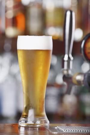 near beer: Schooner glass of Ice Cold Beer sitting on bar top near beer pouring tap Stock Photo
