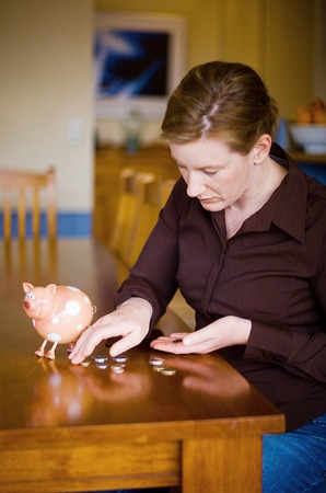 meagre: Adult female emptying money out of Toy money box, sitting at Kitchen table