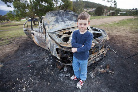 deliberately: Young boy withl uxury model car destroyed in a fire deliberately lit by vandals