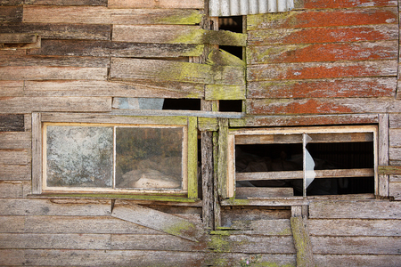 paredes exteriores: Detail of windows and timber exterior walls of a derelict farm building Foto de archivo