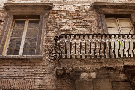 township: Detail of wrought iron balcony and windows in the old township of Perugia in the Umbrian region of Italy Stock Photo
