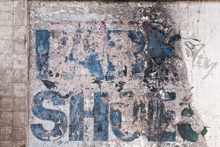 unreadable: Very faded and old advertising sign, now unreadable on a building exterior wall