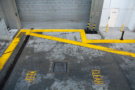 loading bay: Keep Clear road markings painted in yellow lines in a laneway with loading bay access for trucks