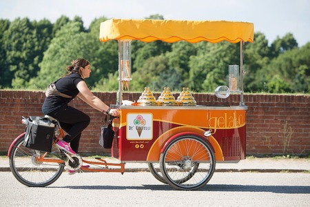 top 7: Lucca, Italy-June 7, 2015. Ice Cream Vendor riding her tricycle cart on top of the wall surrounding the ancient city of Lucca, Italy Editorial