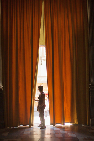 worshipper: Florence, Italy-June 2, 2015. Visitor to a church in Florence entering through the very large curtains