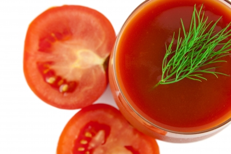 a top view of glass of tomato juice with dill and split tomatoes isolated over white photo