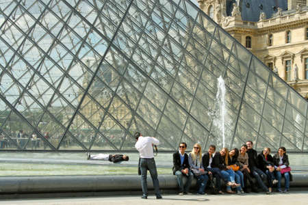 PARIS - MAY 16:  An international group of tourists poses for a picture in front of The Louvre Pyramid on May 16, 2010.