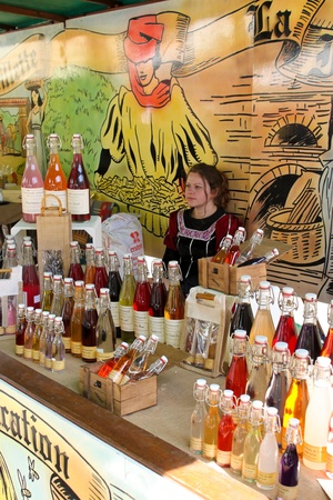 flavorings: COMPIEGNE, FRANCE - MAY 22: An unidentified girl sells syrups and flavorings in a stall on a medieval market held during annual Joan of Arc festival  on May 22, 2010 in Compiegne, France.