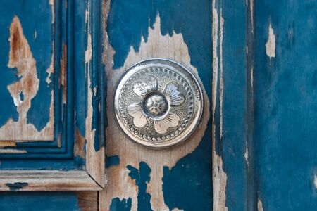 Silver metal door knob on an old wooden door photo