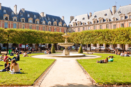 PARIS, FRANCE - SEPTEMBER, 24: People relaxing on green lawns of the famous Place des Vosges - the oldest planned square in Paris on September 24, 2013 in Paris. Editorial